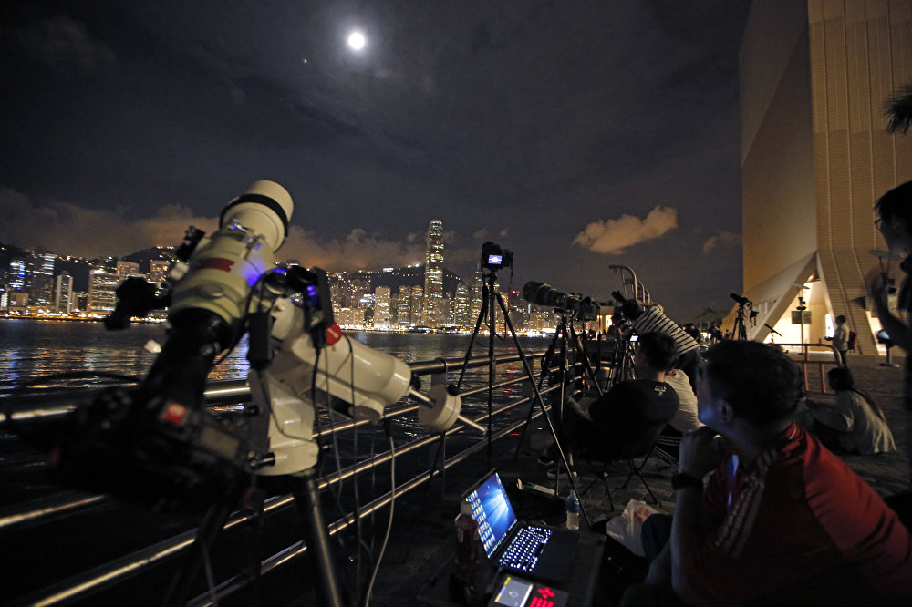 Адамдар айдың тұтылуын телескоппен бақылауда. Гонконг, Қытай.