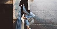 Девушка в рваных джинсах, иллюстративное фото