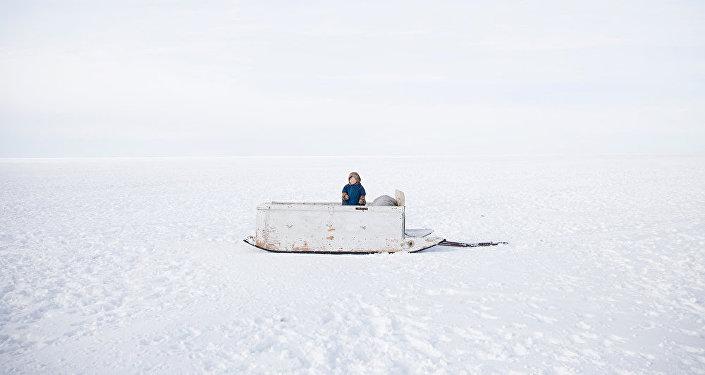 Ребенок из семьи Серотетто, которая принадлежит к племени ненецких кочевников,  на семейных деревянных санях пересекает Обь.  Ямал, Сибирь, Россия.