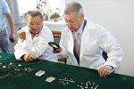 Известный казахстанский археолог Зейнолла Самашев (слева)  презентовал главе региона Даниалу Ахметову уникальные находки