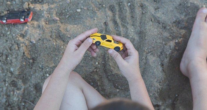 Ребенок держит в руках машинку