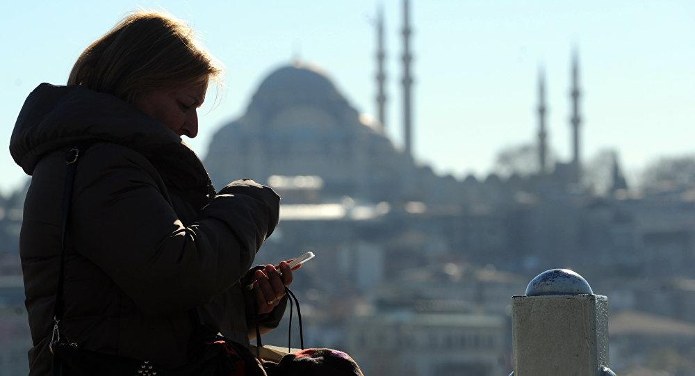 Турецкая женщина смотрит на свой айфон в Стамбуле на фоне мечети, архивное фото