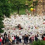 Люди несут цветы к воротам Кенсингтонского дворца накануне похорошо принцессы Дианы