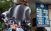 Пожилая женщина смотрит на табло с курсом валют