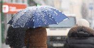 Мужчина с зонтом во время снегопада, архивное фото