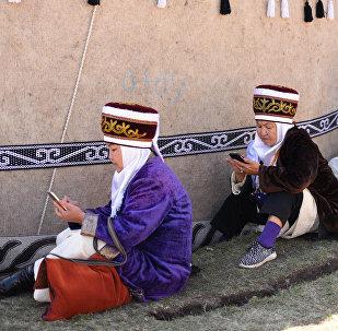 Женщины в национальных костюмах с гаджетами в руках во время Всемирных игр кочевников