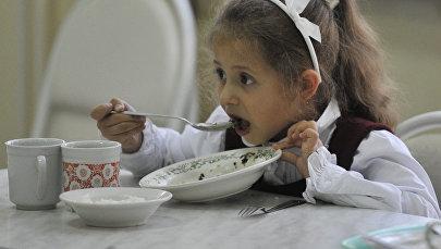 Ребенок обедает в школьной столовой, архивное фото