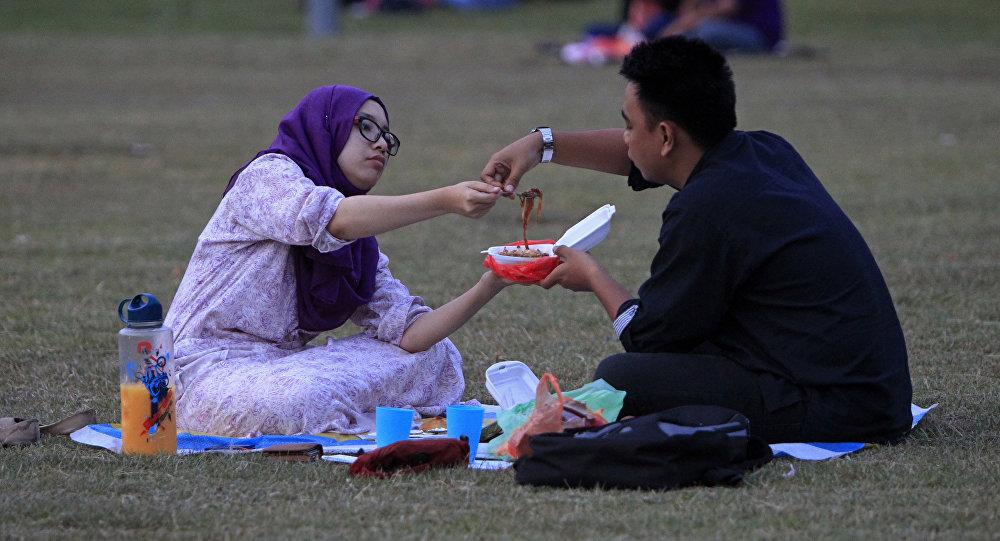 Мужчина и женщина едят в парке, архивное фото