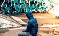 Человек в капюшоне на фоне граффити