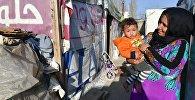 Женщина с ребенком в палаточном лагере для сирийских беженцев, архивное фото