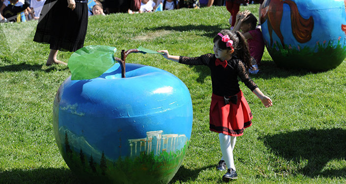 Девочка возле арт-объекта в виде яблока