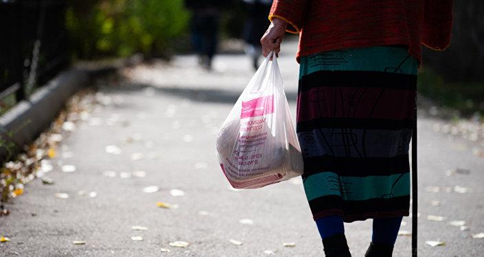 Пожилая женщина несет в пакете продукты