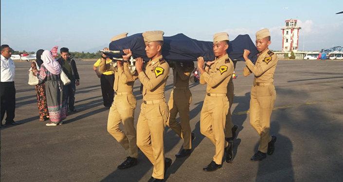 Әуе диспетчері Антониус Гунаван Агунгтың мәйітін алып бара жатыр