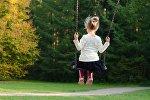Девочка катается на качелях