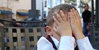 Мальчик закрывает лицо, иллюстративное фото