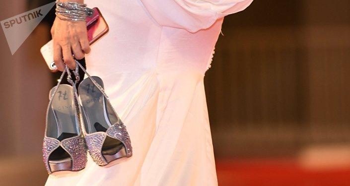 Женщина держит туфли в руках