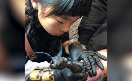 Девятилетняя девочка рисует татуировки