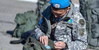 Военнослужащий пришивает шеврон миротворца