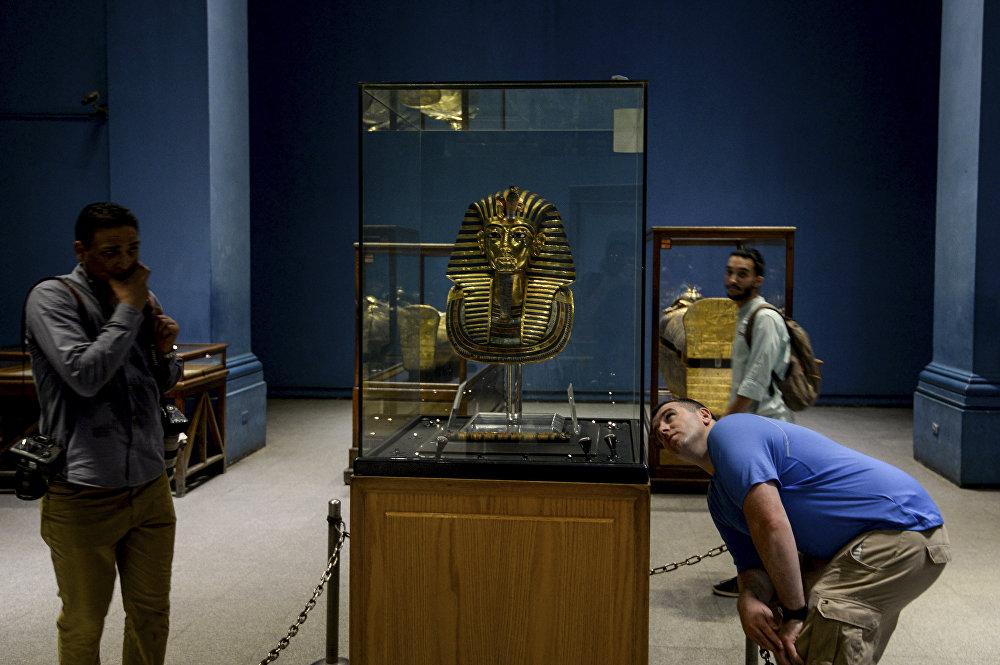 Посетители смотрят на Золотую маску короля Тутанхамона в Египетском музее на Каирской площади Тахрир 5 августа 2018 года