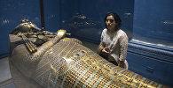 Женщина рассматривает золотой саркофаг фараона Тутанхамона, выставленный в Египетском музее в столице Каире