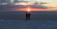 Люди на берегу замерзшей реки, архивное фото