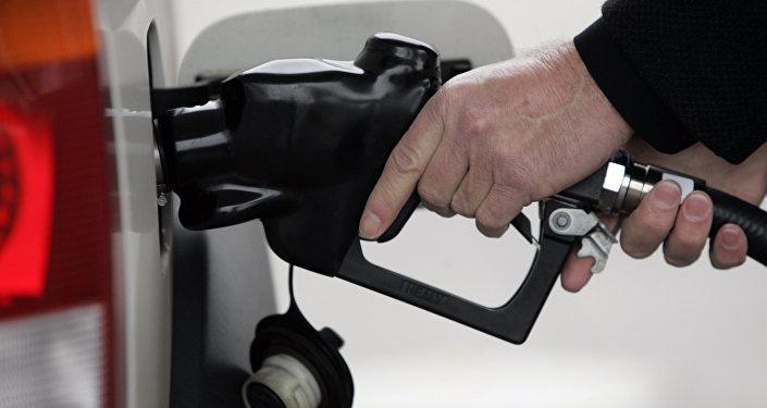Сотрудник автозаправочной станции заправляет автомобиль топливом