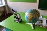 Архивное фото глобуса и микроскопа в школьном кабинете