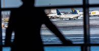 Пассажир смотрит на самолеты в аэропорту