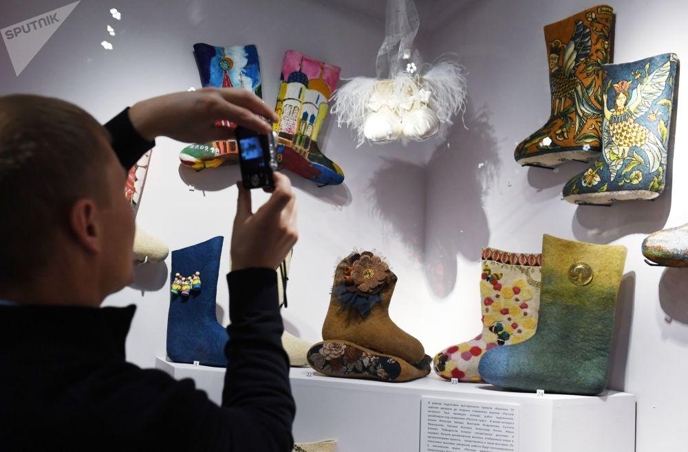 Посетитель фотографирует дизайнерские валенки на выставке Валенки. От царских дворцов до модных подиумов в Малом выставочном зале дворца царя Алексея Михайловича в Коломенском