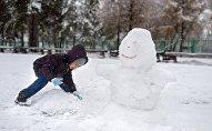 Ребенок лепит снеговика, иллюстративное фото