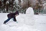 Ребенок лепит снеговика