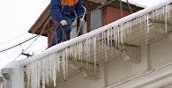 Работник жилищно-коммунальной службы сбивает сосульки с крыши, архивное фото