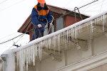 Работник жилищно-коммунальной службы сбивает сосульки с крыши