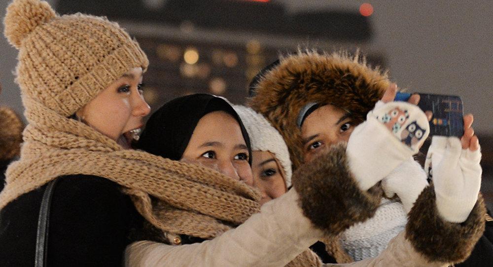 Девушки фотографируются на мобильный телефон, архивное фото