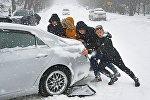 Люди толкают машину
