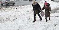 Пешеходы идут по глубокому снегу, архивное фото