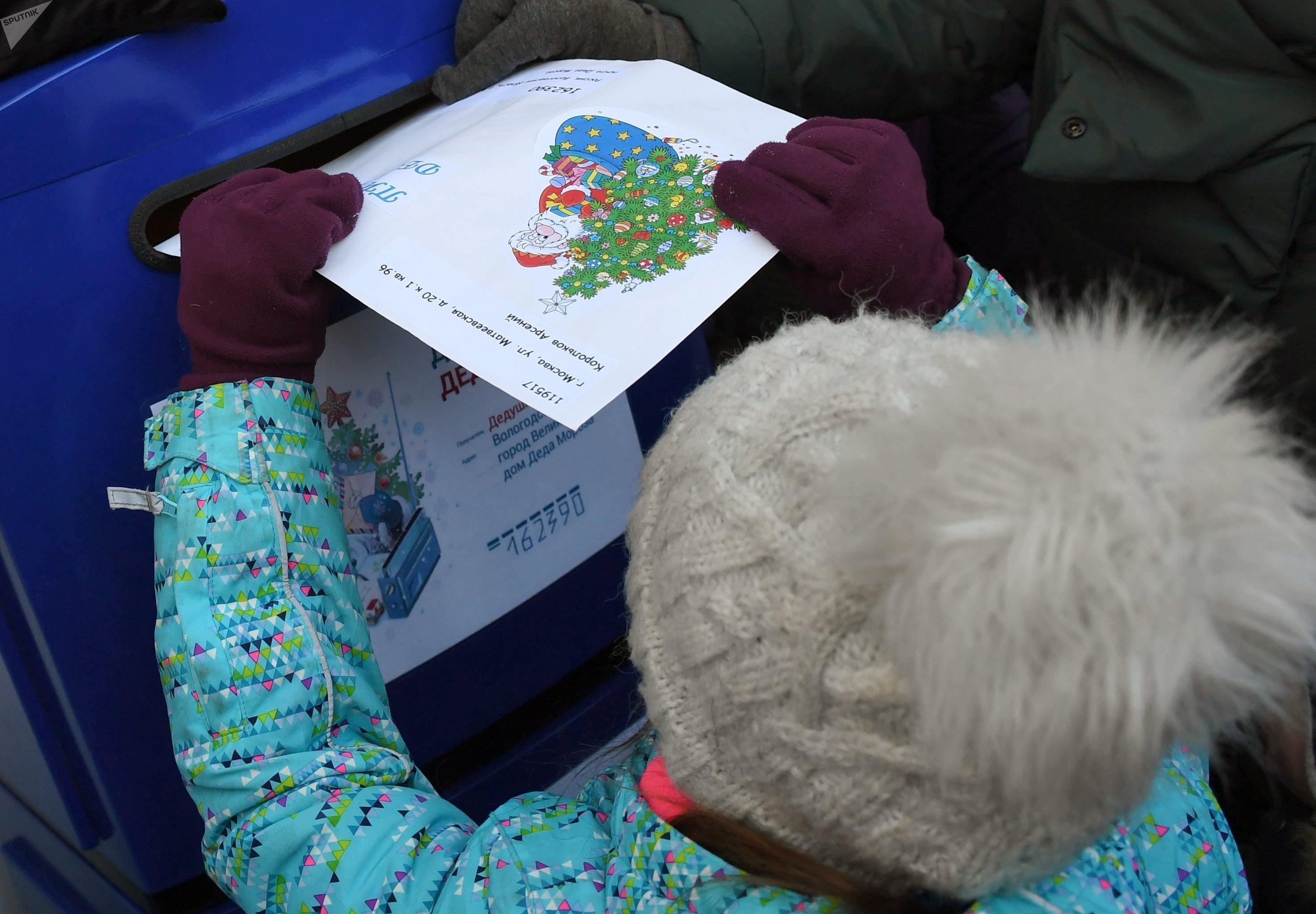 Девочка опускает письмо для Деда Мороза в почтовый ящик