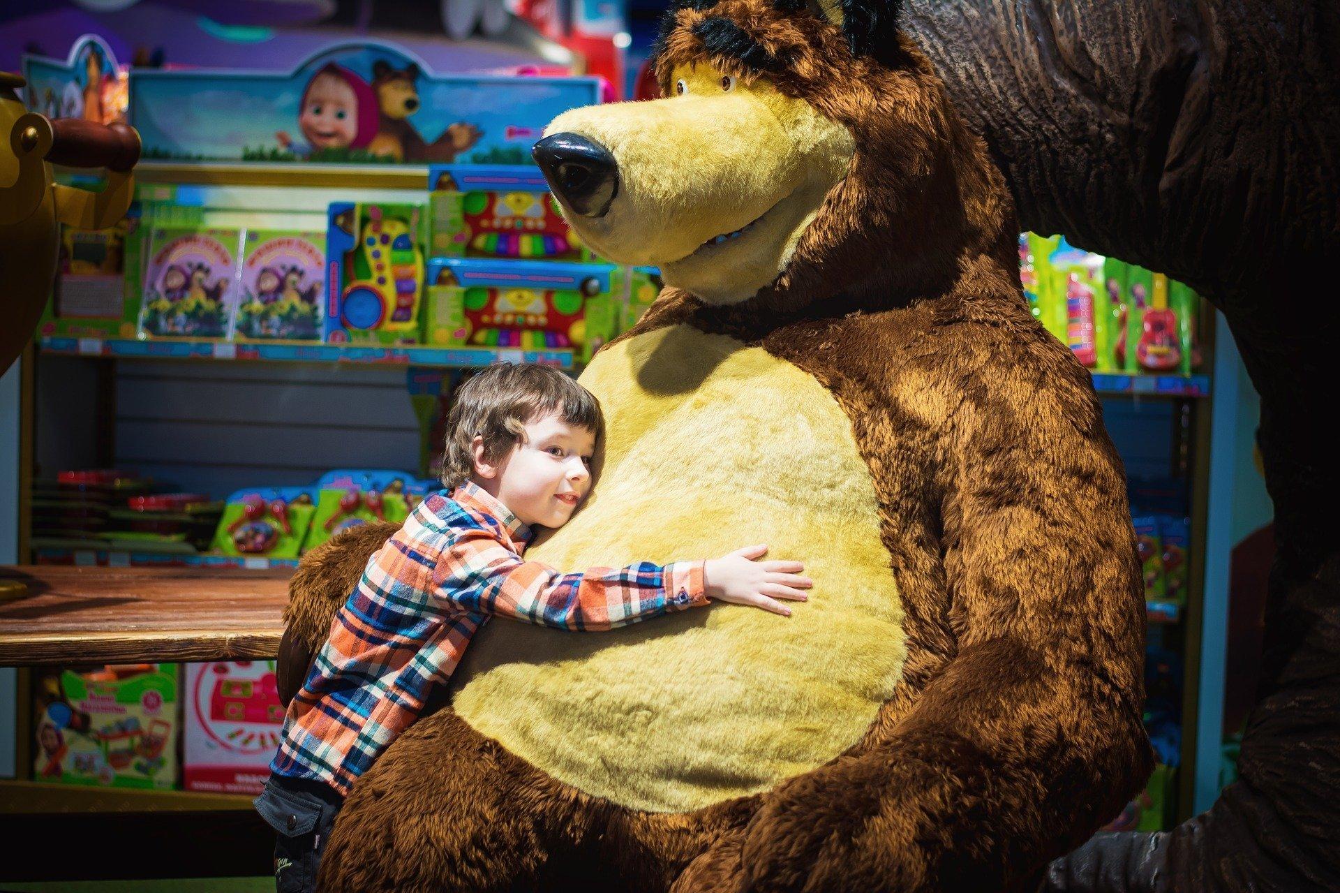Ребенок обнимает игрушечного медведя