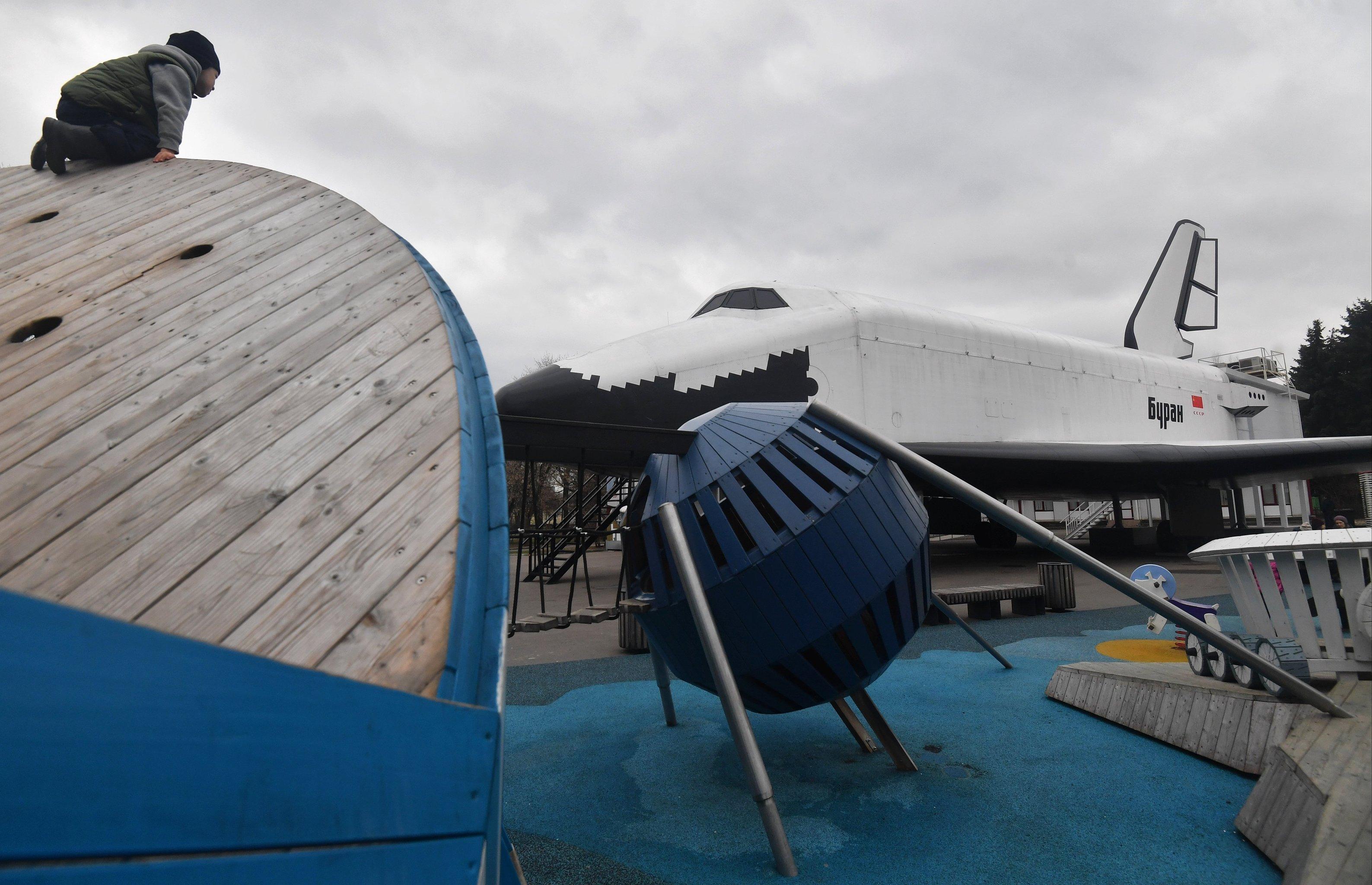 Ребенок на детской площадке рядом с павильоном Космос на территории ВДНХ