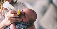 Женщина кормит малыша, иллюстративное фото