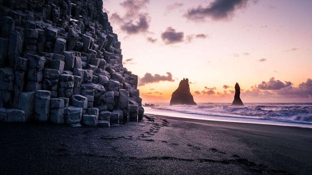 Рассвет на ппяже Рейнисфьяра с черным вулканическим песком в Исландии