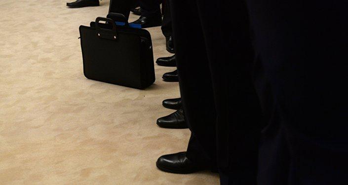 Архивное фото портфеля в кругу мужчин в деловых костюмах