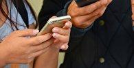 Телефон ұстап тұрған адамдар