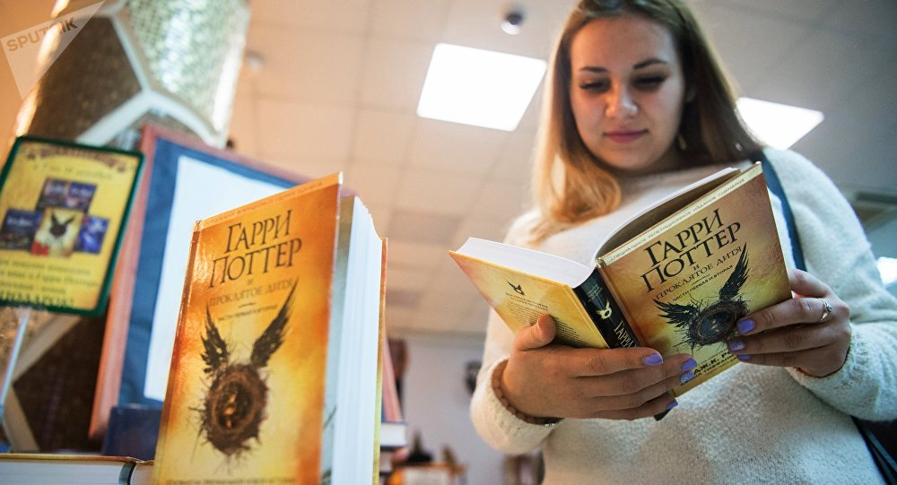 Девушка читает книгу о приключениях Гарри Поттера, архивное фото