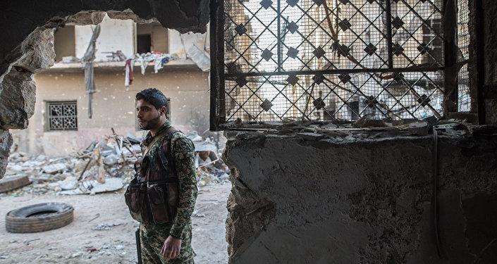 Военнослужащий Сирийской Арабской армии в жилом квартале города Алеппо, через который проходит линия фронта
