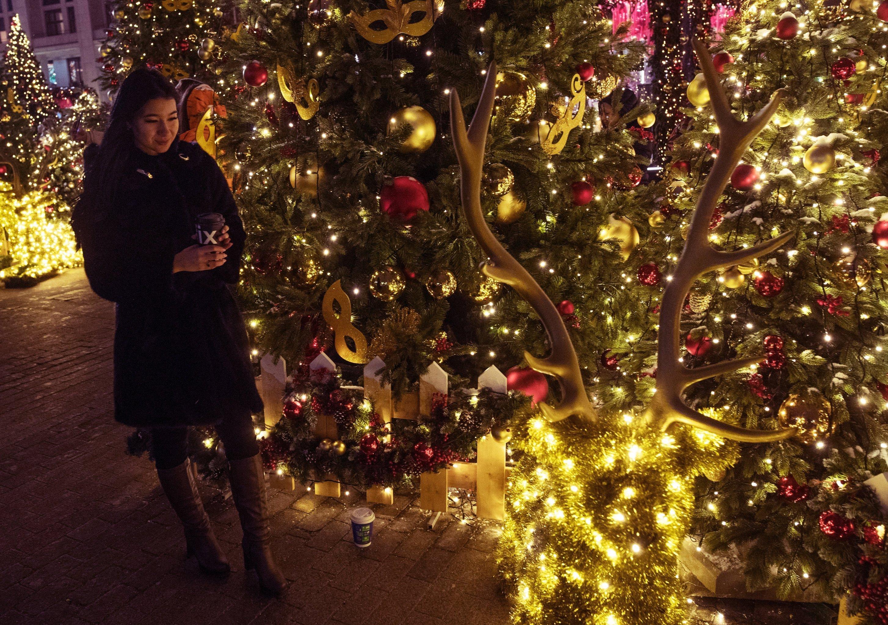 Турист қыз Манежный алаңында жаңажылдық декорацияның ортасында тұр