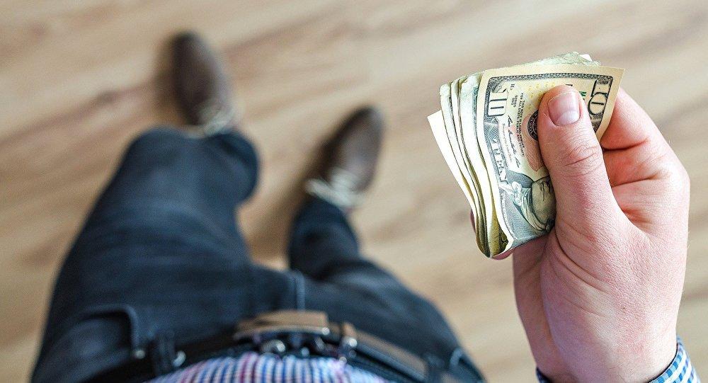 Мужчина держит доллары
