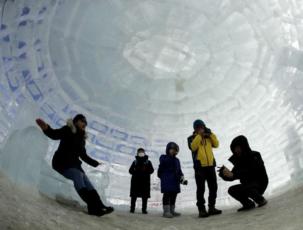 Люди фотографируются в иглу, построенного для зимних Олимпийских игр 2018 года в Пхенчхане, Южная Корея