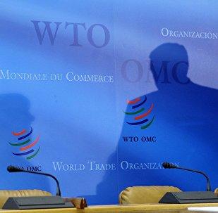 Архивное фото логотипов Всемирной торговой организации (ВТО), на фоне которых просматриваются тени делегатов министерского саммита в штаб-квартире в Женеве