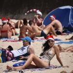 Австралия жағажайында рождество бас киімін киген турист әйел.